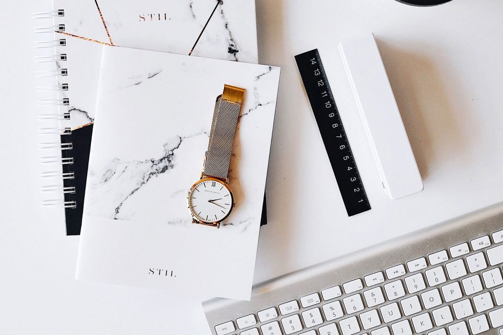Beautiful white flatlay with gold watch silver keyboard and white and black marble journals
