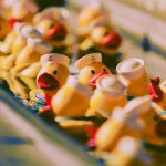 Yellow rubber ducks with red beaks and white sailor hats in a tub