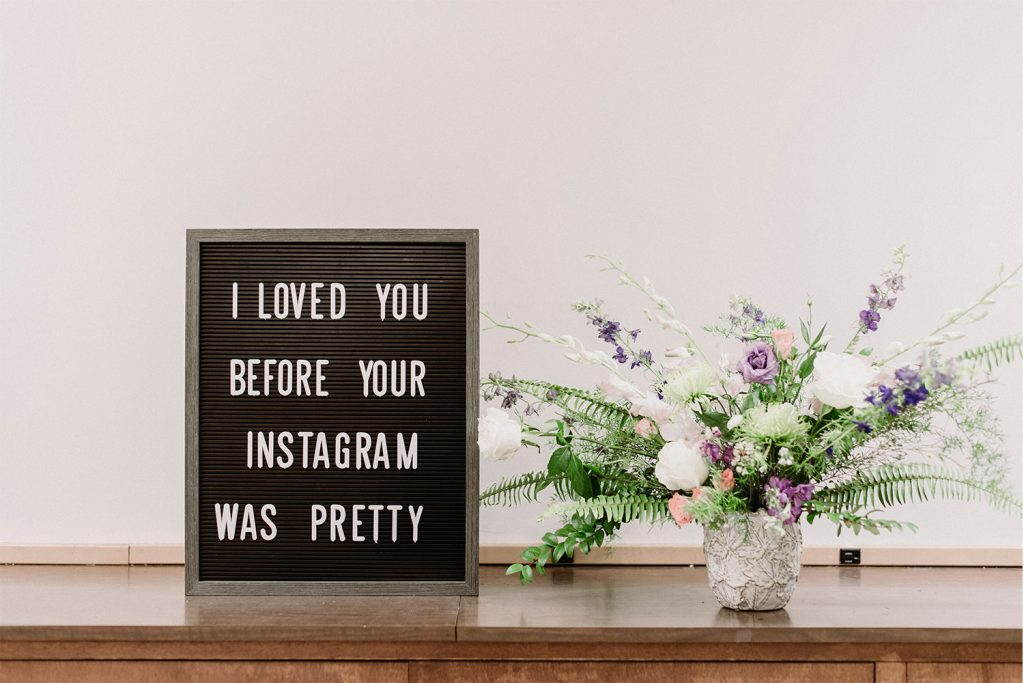 A black board sign that say I loveed you before your Instagram was pretty on a table with white flowers